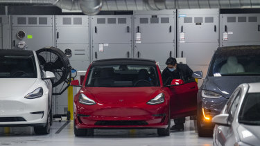 A worker wearing a protective mask cleans a Tesla Inc. vehicle at a store in San Francisco on Tuesday.